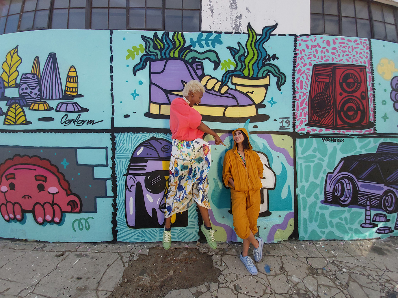 Photo captured by Galaxy A80's Ultra Wide Camera of the two women and graffiti wall in full view.