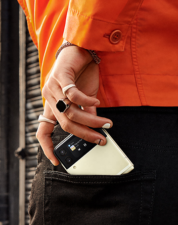 The man's hand, pushing Galaxy Z Flip3 5G into the back pocket of his jeans.
