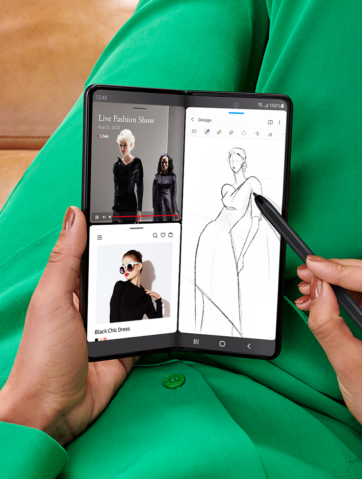 Hands holding unfolded Galaxy Z Fold3 5G and sketching with the S Pen Fold Edition. The Main Screen is in Multi Active Window mode. One half of the screen shows two instances of the Internet app open, one with a live stream of a fashion show and the other with a website showing images of the garments from the show. The other half of the screen is a sketch of a dress being done in Samsung Notes.